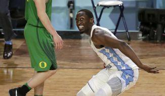 North Carolina's Theo Pinson, right, celebrates as Oregon's Payton Pritchard walks off the court after the semifinals of the Final Four NCAA college basketball tournament, Saturday, April 1, 2017, in Glendale, Ariz. North Carolina won 77-76. (AP Photo/Matt York)
