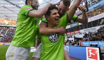 Wolfsburg's Mario Gomez, center, celebrates his third goal with team mates during the German Bundesliga soccer match between Bayer Leverkusen and VfL Wolfsburg in Leverkusen, Germany, Sunday, April 2, 2017. The match ended 3-3, Gomez scored a hattrick. (AP Photo/Martin Meissner)