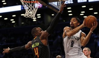 Brooklyn Nets guard Spencer Dinwiddie (8) looks to pass around Atlanta Hawks forward Paul Millsap (4) during the first half of an NBA basketball game Sunday, April 2, 2017, in New York. (AP Photo/Adam Hunger)
