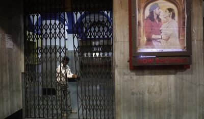 In this early Friday, March 31, 2017 photo, a guard locks the gate after the last movie screening at iconic Regal Theater in New Delhi, India. From Bollywood superstars to political heavyweights, the theater had hosted some of India's biggest names over more than eight decades. But with nostalgic theater-goers singing their way to the exits after a final showing of a Bollywood classic, the New Delhi theater has closed its doors to make way for a multiplex. (AP Photo/Manish Swarup)