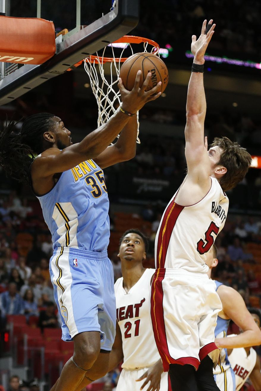 Miami Heat's Hassan Whiteside (21) looks up as Heat's Luke Babbitt (5) defends against a shot by Denver Nuggets Kenneth Faried (35) during the first half of an NBA basketball game, Sunday, April 2, 2017, in Miami, Fla. (AP Photo/Joel Auerbach)