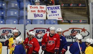 In this Thursday, March 30, 2017, photo, U.S. teammates practice with fans holding support signs in preparation for the IIHF Women's World Championship hockey tournament in Plymouth, Mich. USA Hockey and the women's national team agreed to a contract Tuesday, March 28 that ended a wage dispute. (AP Photo/Paul Sancya)