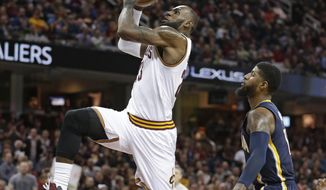 Cleveland Cavaliers' LeBron James, left, drives to the basket against Indiana Pacers' Paul George in the first half of an NBA basketball game, Sunday, April 2, 2017, in Cleveland. (AP Photo/Tony Dejak)