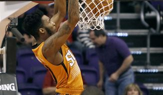 Phoenix Suns' Derrick Jones Jr., top, dunks the ball in front of Houston Rockets' Eric Gordon during the first half of an NBA basketball game, Sunday, April 2, 2017, in Phoenix. (AP Photo/Ralph Freso)