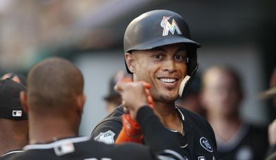 Miami Marlins' Giancarlo Stanton (27) celebrates after hitting a two-run home run in the first before a spring training baseball game against the Detroit Tigers, Friday, March 31, 2017, in Jupiter, Fla. (AP Photo/John Bazemore)