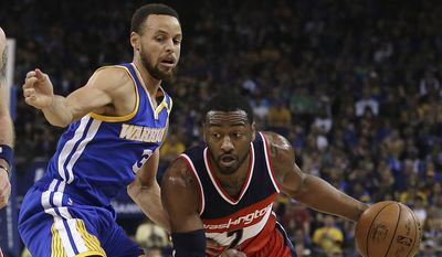 Washington Wizards' John Wall, right, drives the ball around Golden State Warriors' Stephen Curry during the first half of an NBA basketball game Sunday, April 2, 2017, in Oakland, Calif. (AP Photo/Ben Margot)