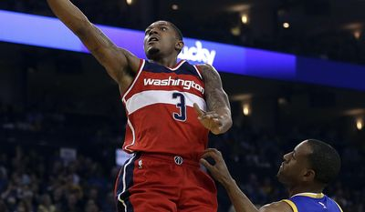 Washington Wizards' Bradley Beal (3) lays up a shot over Golden State Warriors' Andre Iguodala, right, during the first half of an NBA basketball game Sunday, April 2, 2017, in Oakland, Calif. (AP Photo/Ben Margot)