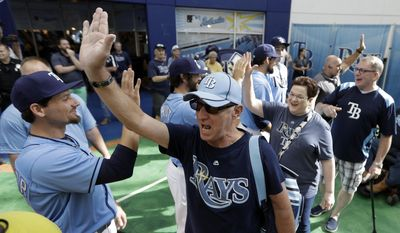 Tampa Bay Rays fans high-five players, including relief pitcher Danny Farquhar, left, as the gates open before an Opening Day baseball game between the Rays and the New York Yankees, Sunday, April 2, 2017, in St. Petersburg, Fla. (AP Photo/Chris O'Meara)