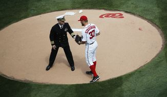 U.S. Navy Capt. Jeffrey Draeger, hands the ball to Washington Nationals starting pitcher Stephen Strasburg (37) during ceremonial game ball delivery at the opening day baseball game between the Washington Nationals and Miami Marlins in Washington, Monday, April 3, 2017.   (AP Photo/Manuel Balce Ceneta)
