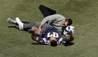 New England Patriots quarterback Tom Brady, left, tackles tight end Rob Gronkowski, right, who had grabbed Brady's recovered jersey, which was stolen from the locker room after the Patriots' February Super Bowl victory over the Atlanta Falcons in Houston, during pregame ceremonies before a baseball game between the Boston Red Sox and the Pittsburgh Pirates on opening day at Fenway Park, Monday, April 3, 2017, in Boston. (AP Photo/Steven Senne)