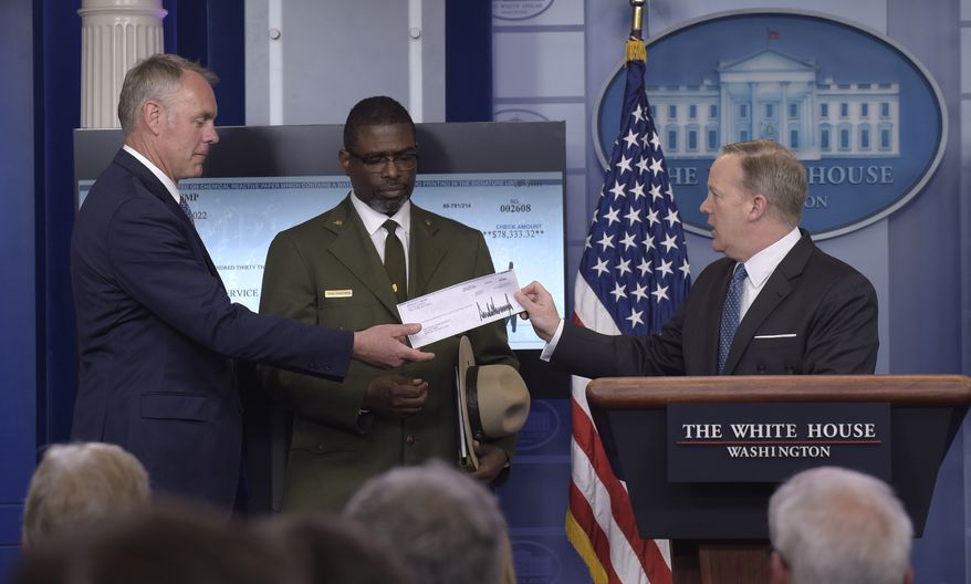 White House press secretary Sean Spicer, right, holds up a check during the daily briefing with Interior Secretary Ryan Zinke, left, and Harpers Ferry National Historic Park Superintendent Tyrone Brandyburg, center, at the White House in Washington, Monday, April 3, 2017. President Donald Trump gave his first quarter salary to the National Park Service. (AP Photo/Susan Walsh)