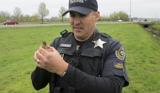 CORRECTS DATE TO APRIL 1 - In this Saturday, April 1, 2017 photo provided by the Oregon State Police, Oregon State Police Sr. Trooper Hunter, of the agency's fish and wildlife division, holds a duckling he helped rescue from a storm drain in Salem, Ore. Witnesses said a mother duck and her 10 ducklings were crossing the street at an intersection when two of the ducklings were swept into a storm drain. Hunter fished the ducklings from the drain with a net after city public works staffers removed several storm grates and a manhole cover. The babies were successfully reunited with their mother and siblings. (Oregon State Police via AP)