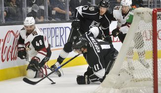 Arizona Coyotes left wing Jordan Martinook (48), of Canada, vies for the puck with Los Angeles center Anze Kopitar (11), of Yugoslavia, during the first period of an NHL hockey game Sunday, April 2, 2017, in Los Angeles. Kings defenseman Brayden McNabb (3), and Coyote Right wing Josh Joonis, of Canada, move in on the play. (AP Photo/Richard Hartog)
