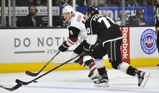 Arizona Coyote center Christian Dvorak (18) controls the puck in front of Los Angeles Kings left wing Tanner Person, right, during the first period of an NHL hockey game Sunday, April 2, 2017, in Los Angeles. (AP Photo/Richard Hartog)
