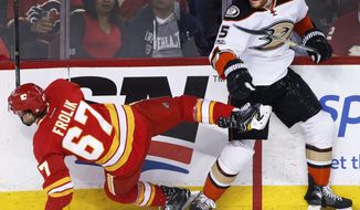 Anaheim Ducks' Korbinian Holzer, right, from Germany, knocks down Calgary Flames' Michael Frolik, from the Czech Republic, during the first period of an NHL hockey game Sunday, April 2, 2017, in Calgary, Alberta. (Larry MacDougal/The Canadian Press via AP)