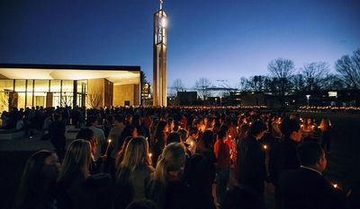 In this April 2, 2017 photo released by Sacred Heart University, students participate in a candlelight vigil in memory of student Caitlin Nelson on the school's campus in Fairfield, Conn. Police said Nelson, from Clark, N.J., died three days after choking during a pancake-eating contest at the college. (Sean Kaschak/Sacred Heart University via AP)