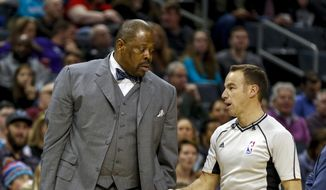 FILE - In this Jan. 28, 2017, file photo, Charlotte Hornets assistant coach Patrick Ewing, left, talks to NBA referee Josh Tiven as the Hornets play the Sacramento Kings in a NBA basketball game in Charlotte, N.C. A person with direct knowledge of the situation says former Georgetown star Patrick Ewing has been hired to coach the school's basketball team, more than two decades after he led the Hoyas to their only national championship as a player.The person spoke to The Associated Press on condition of anonymity because the school has not announced the hire.AP Photo/Nell Redmond, File) **FILE**