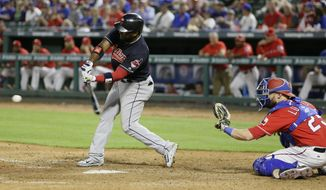 Cleveland Indians Abraham Almonte, left, hits an RBI single in front of Texas Rangers catcher Jonathan Lucroy (25) during the ninth inning of an opening day baseball game in Arlington, Texas, Monday, April 3, 2017. Indians Tyler Naquin scored on the play and the Indians won 8-5. (AP Photo/LM Otero)