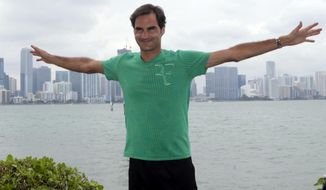 Roger Federer, of Switzerland, poses for a photograph in front of the Miami skyline after defeating Rafael Nadal in the men's singles final at the Miami Open tennis tournament, Sunday, April 2, 2017, in Miami. (AP Photo/Lynne Sladky)