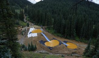 In this Aug. 12, 2015 photo, mine wastewater flows through a series of retention ponds built to contain and filter out heavy metals and chemicals from the Gold King Mine chemical accident in the spillway about 1/4 mile downstream from the mine, outside Silverton, Colo. Farmers, business owners and residents initially said they suffered $1.2 billion in lost income, property damage and personal injuries from the 2015 spill at the Gold King Mine. The total now appears to be about $420 million after attorneys for a handful of New Mexico property owners slashed their claims by $780 million. (AP Photo/Brennan Linsley)