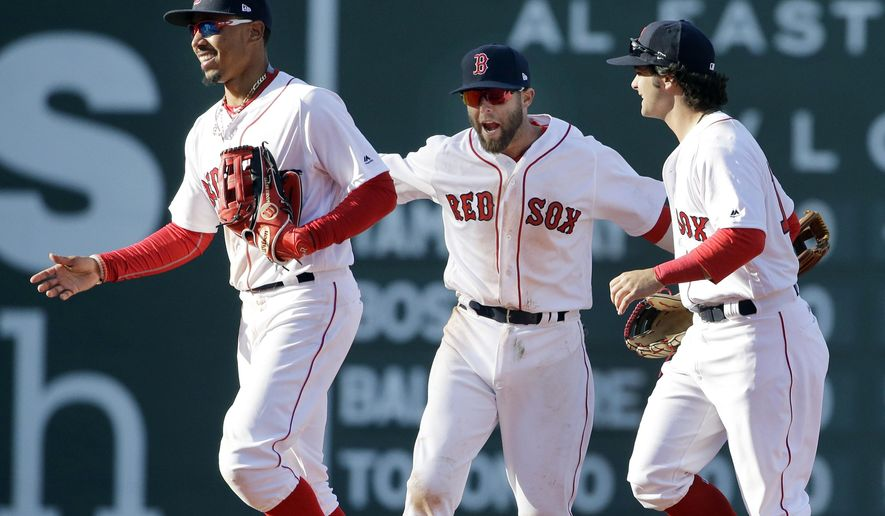 Boston Red Sox, from left, Mookie Betts, Dustin Pedroia and Andrew Benintendi celebrate after a baseball game against the Pittsburgh Pirates at Fenway Park, Monday, April 3, 2017, in Boston. The Red Sox won 5-3. (AP Photo/Elise Amendola)