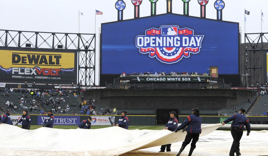 The grounds crew puts a tarp on the field at Guaranteed Rate Field during a rain delay before an MLB baseball game between the Chicago White Sox and Detroit Tigers on opening day Monday, April 3, 2017 in Chicago. (AP Photo/Paul Beaty)