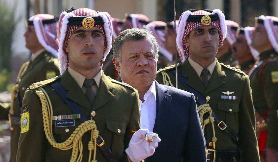 In this Jan. 23, 2016 file photo, Jordan's King Abdullah II, second left, reviews an honor guard during a celebrations marking the centennial of the Arab Revolt against the region's ruling Ottoman Turks, in Jordan's Red Sea port of Aqaba. (AP Photo/Raad Adayleh, Pool, File)