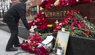 A man lays flowers in memory of victims killed by a bomb blast in a subway train in St. Petersburg, at the memorial stone with the word Leningrad (St. Petersburg) at the Tomb of Unknown Soldier, in front of the Kremlin wall in Moscow, Russia, Tuesday, April 4, 2017. A bomb blast tore through a subway train deep under Russia's second-largest city St. Petersburg Monday, killing several people and wounding many more in a chaotic scene that left victims sprawled on a smoky platform. (AP Photo/Pavel Golovkin)