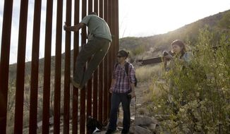 Tim Foley shows how to climb a section of the border wall separating Mexico and the United States near where it ends as journalists Chitose Nakagawa (right) and Marcie Mieko Kagawa look on in Sasabe, Ariz., in this May 11, 2016, photo. Mr. Foley, a former construction foreman, founded Arizona Border Recon, a group of armed volunteers who dedicate themselves to border surveillance. (Associated Press) **FILE**