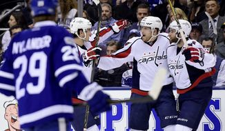 Toronto Maple Leafs center William Nylander (29) skates past as Washington Capitals right wing Brett Connolly (10) and left wing Andre Burakovsky (65) celebrate with center Lars Eller (20) after Eller's goal during the first period of an NHL hockey game Tuesday, April 4, 2017, in Toronto. (Frank Gunn/The Canadian Press via AP)