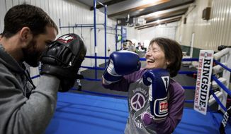 In this March 8, 2017, photo, Barb Halleen who is battling Parkinson's disease, spars  with volunteer coach Jimmy Lyons as part of the Rock Steady Boxing program at CrossFit 309 in Peoria Heights, Ill. The Rock Steady program is growing, offering people with Parkinson's a way to push themselves to fight back against the disease by boxing. This year, they've expanded to more classes, moved into their own dedicated space at CrossFit, and just recently installed a professional boxing ring. (Fred Zwicky/Journal Star via AP) ** FILE **