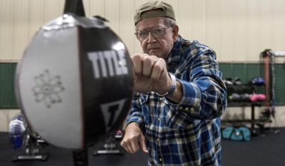 In this March 8, 2017 photo, Steve Johnson who is battling Parkinson's disease works  on his technique as part of the he Rock Steady Boxing program at CrossFit 309 in Peoria Heights, Ill. The Rock Steady program is growing, offering people with Parkinson's a way to push themselves to fight back against the disease by boxing. This year, they've expanded to more classes, moved into their own dedicated space at CrossFit, and just recently installed a professional boxing ring.(Fred Zwicky/Journal Star via AP)
