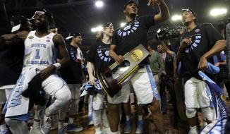 North Carolina's Kennedy Meeks holds the championship trophy as he celebrates with his teammates after the finals of the Final Four NCAA college basketball tournament against Gonzaga, Monday, April 3, 2017, in Glendale, Ariz. North Carolina won 71-65. (AP Photo/David J. Phillip)