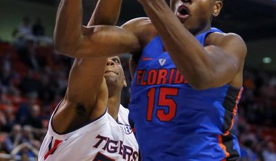"""In this Tuesday, Feb. 14, 2017, photo, Florida center John Egbunu (15) grabs a rebound away from Auburn center Austin Wiley (50) during the first half of an NCAA college basketball game in Auburn, Ala. Florida coach Mike White might be facing a bigger rebuilding project than initially expected. White said Tuesday, April 4, that injured center Egbunu plans to """"test the waters"""" of the NBA draft. Egbunu doesn't intend to hire an agent, meaning he could end up returning to school for his final year of eligibility. (AP Photo/Butch Dill)"""