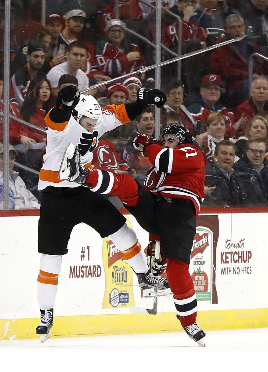 Philadelphia Flyers defenseman Shayne Gostisbehere, left, and New Jersey Devils right wing Kyle Palmieri collide while competing for the puck during the second period of an NHL hockey game, Tuesday, April 4, 2017, in Newark, N.J. (AP Photo/Julio Cortez)