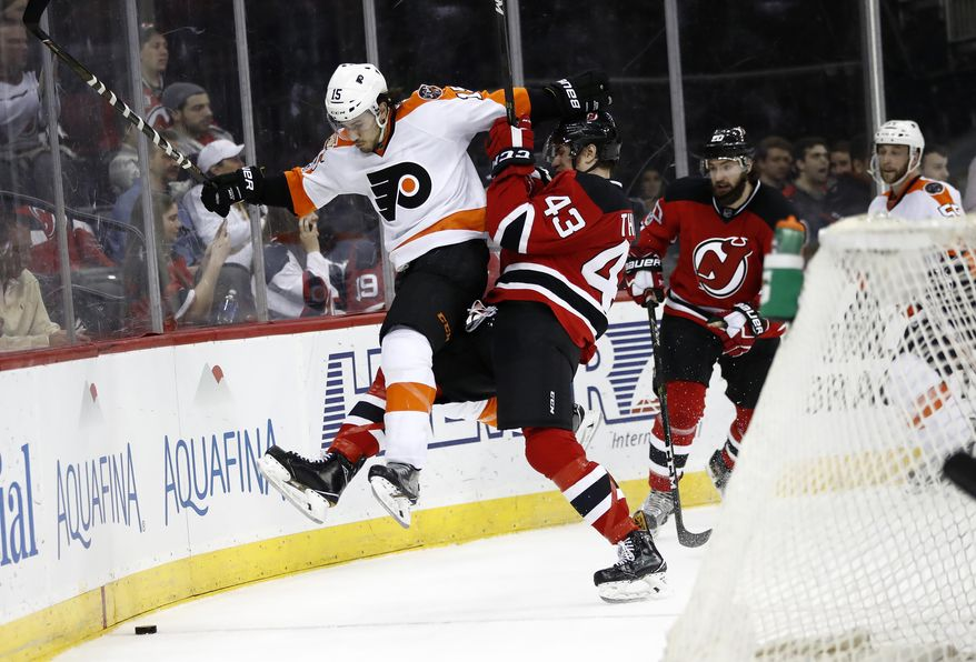Philadelphia Flyers defenseman Michael Del Zotto (15) is checked by New Jersey Devils right winger Ben Thomson (43) during the second period of an NHL hockey game, Tuesday, April 4, 2017, in Newark, N.J. (AP Photo/Julio Cortez)