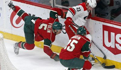 Minnesota Wild's Christian Folin, left, of Sweden, gets tripped up chasing the puck with Carolina Hurricanes' Brock McGinn in the first period of an NHL hockey game Tuesday, April 4, 2017, in St. Paul, Minn. (AP Photo/Jim Mone)