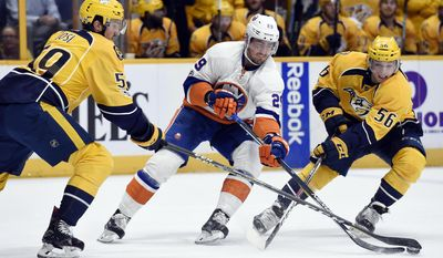 New York Islanders center Brock Nelson (29) maneuvers the puck between Nashville Predators defenseman Roman Josi (59), of Switzerland, and left wing Kevin Fiala (56), of the Czech Republic, during the first period of an NHL hockey game Tuesday, April 4, 2017, in Nashville, Tenn. (AP Photo/Mark Zaleski)