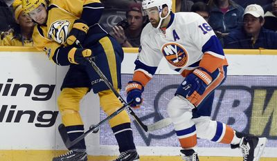 Nashville Predators left wing Filip Forsberg (9), of Sweden, passes the puck away from New York Islanders left wing Andrew Ladd (16) during the first period of an NHL hockey game Tuesday, April 4, 2017, in Nashville, Tenn. (AP Photo/Mark Zaleski)