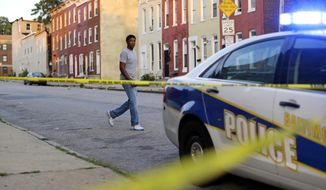 FILE - In this July 30, 2015 file photo, a man walks past a corner where a victim of a shooting was discovered in Baltimore. In a city that became emblematic of police abuse, excessive force and callous treatment of young black men, Baltimore's mayor and commissioner say they are eager and ready to change not only the culture of law enforcement, but the practice. (AP Photo/Patrick Semansky, File)