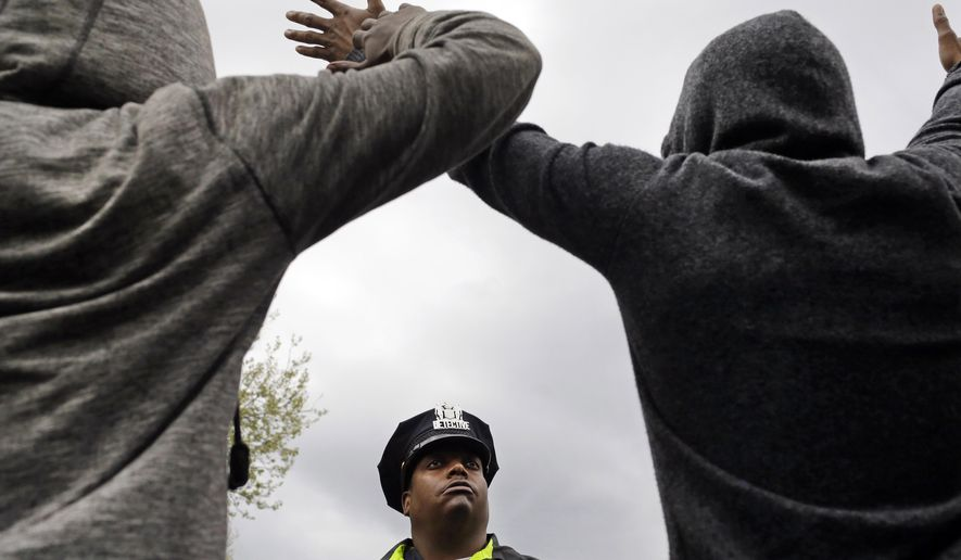 FILE - In this April 22, 2015 file photo, a member of the Baltimore Police Department stands guard outside of the department's Western District police station as men hold their hands up in protest during a march for Freddie Gray in Baltimore. In a city that became emblematic of police abuse, excessive force and callous treatment of young black men, Baltimore's mayor and commissioner say they are eager and ready to change not only the culture of law enforcement, but the practice. (AP Photo/Patrick Semansky, File)