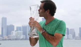 Roger Federer, of Switzerland, poses for a photograph with his trophy in front of the Miami skyline after defeating Rafael Nadal in the men's singles final at the Miami Open tennis tournament, Sunday, April 2, 2017, in Miami. (AP Photo/Lynne Sladky)