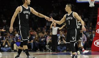 Brooklyn Nets' Brook Lopez, left, slaps hands with Jeremy Lin, right, who scored during the first half of the team's NBA basketball game against the Philadelphia 76ers, Tuesday, April 4, 2017, in Philadelphia. (AP Photo/Chris Szagola)