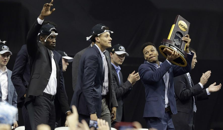 North Carolina's Nate Britt, right, holds the championship trophy as Justin Jackson, center, and Theo Pinson, left, greet fans in Chapel Hill, N.C., Tuesday, April 4, 2017 following Monday's win over Gonzaga in the NCAA college basketball championship. (AP Photo/Gerry Broome)