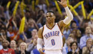 Oklahoma City Thunder guard Russell Westbrook (0) waves to the crowd after tying the record for triple-doubles in a season in the third quarter of an NBA basketball game against the Milwaukee Bucks in Oklahoma City, Tuesday, April 4, 2017. (AP Photo/Sue Ogrocki)