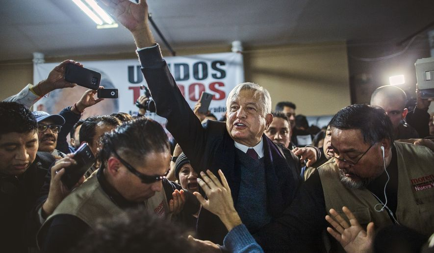 Former Mexican presidential candidate Andres Manuel Lopez Obrador salutes as he leaves in between supporters after speaking about immigration and against U.S. President Donald Trump's policies during a meeting with Mexican migrants at the Shrine of Our Lady of Guadalupe in New York, Monday, March 13, 2017. (AP Photo/Andres Kudacki)
