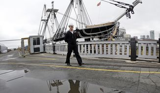 Public Affairs Officer Josh Hammond is reflected in a puddle as restoration work on the USS Constitution continues, Wednesday, April 5, 2017, at the Charlestown Navy Yard in Boston. The ship enters dry dock for below-the-waterline repairs every 20 years. The world's oldest commissioned warship afloat is scheduled to return to the waters in late July. (AP Photo/Elise Amendola)