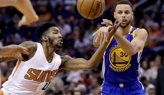 Golden State Warriors guard Stephen Curry (30) passes as Phoenix Suns forward Derrick Jones Jr. defends during the first half of an NBA basketball game, Wednesday, April 5, 2017, in Phoenix. (AP Photo/Matt York)