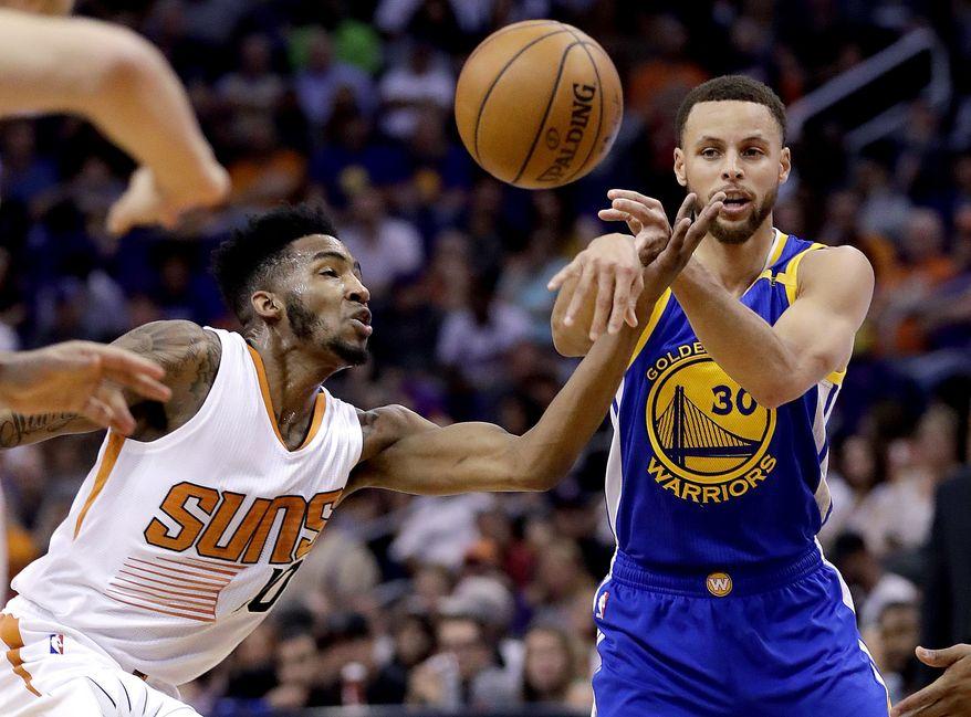 Golden State Warriors guard Stephen Curry (30) passes as Phoenix Suns forward Derrick Jones Jr. defends during the first half of an NBA basketball game, Wednesday, April 5, 2017, in Phoenix. (AP Photo/Matt York)