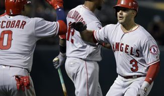 Los Angeles Angels' Danny Espinosa (3) celebrates with Yunel Escobar (0) after hitting a three-run home run off Oakland Athletics' Ryan Dull during the ninth inning of a baseball game Tuesday, April 4, 2017, in Oakland, Calif. (AP Photo/Ben Margot)